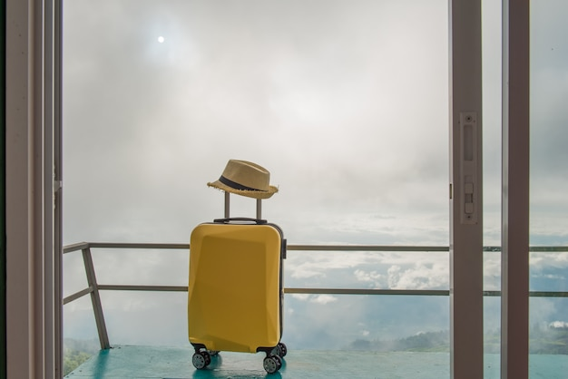 Traveling bag or travel suitcase and hat at the hotel or accommodation with beautiful landscape