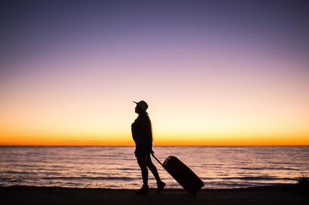 여행, 해변 및 휴가 개념-가방을 당기는 바다 해안을 따라 걷는 여성의 실루엣.