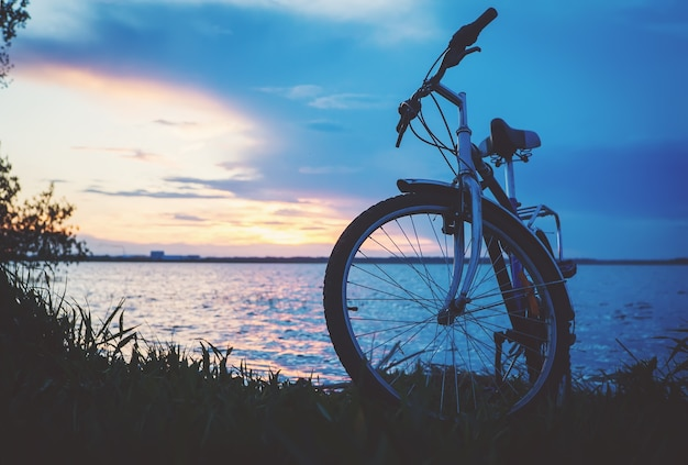 自転車で旅行する。自転車で美しい景色。湖に沈む夕日。自転車のシルエット