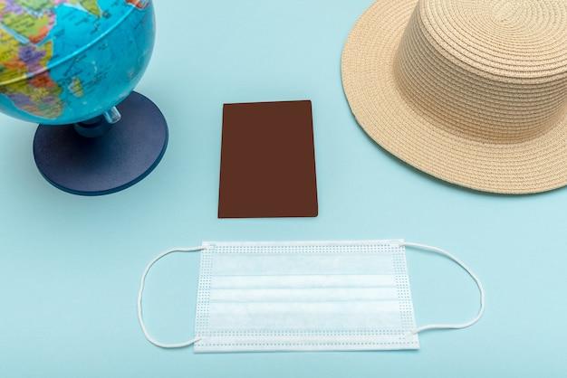 パンデミック時に飛行機で旅行する。グローブ、帽子、パスポート、青い背景のマスク。健康保護。