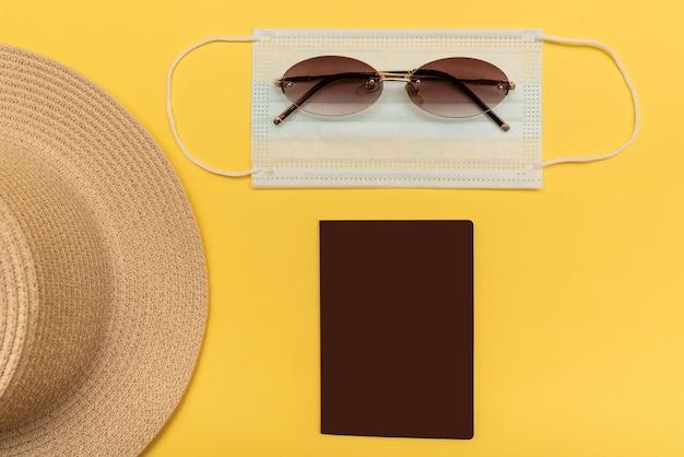 パンデミック時に飛行機で旅行する。黄色の背景に、帽子、パスポート、メガネ、マスク。病気からの保護