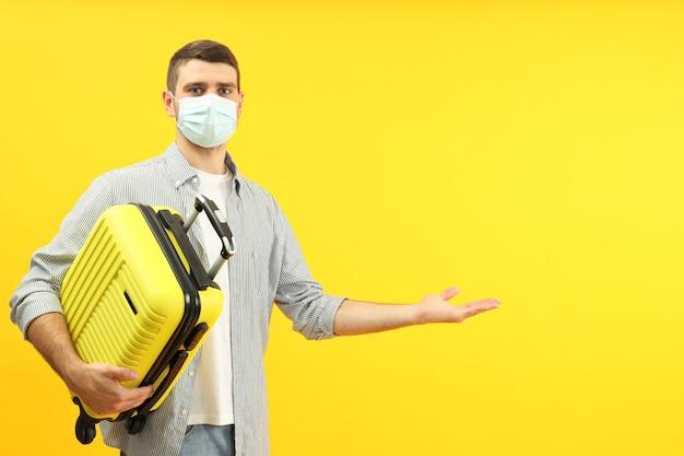 노란색 배경에 젊은 남자와 코로나바이러스 동안 여행 개념.