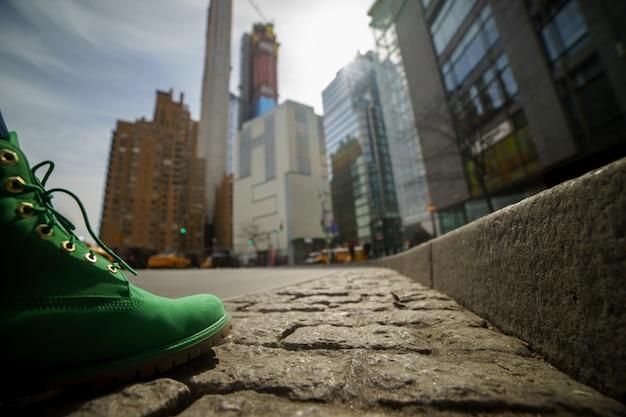 Концепция путешествия. зеленый ботинок заделывают с размытым нью-йорком на фоне.