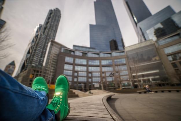 Концепция путешествия. зеленые сапоги заделывают с размытым нью-йорком на фоне.