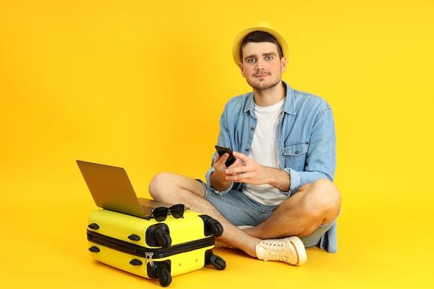 Путешествие концепции с молодым человеком на желтом фоне.