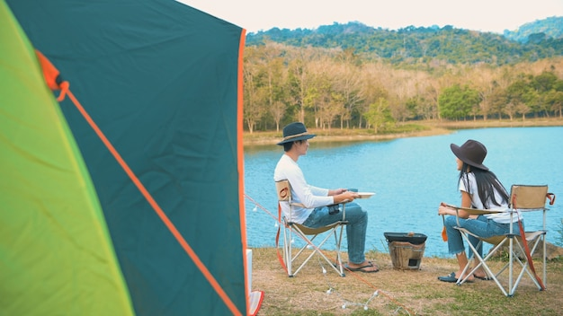 A traveling couple are cooking in camping over lake and mountain view