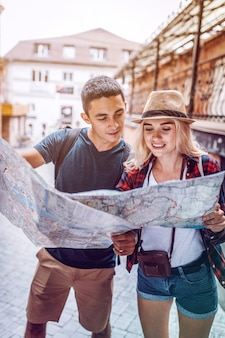 Traveling couple exploring paper map