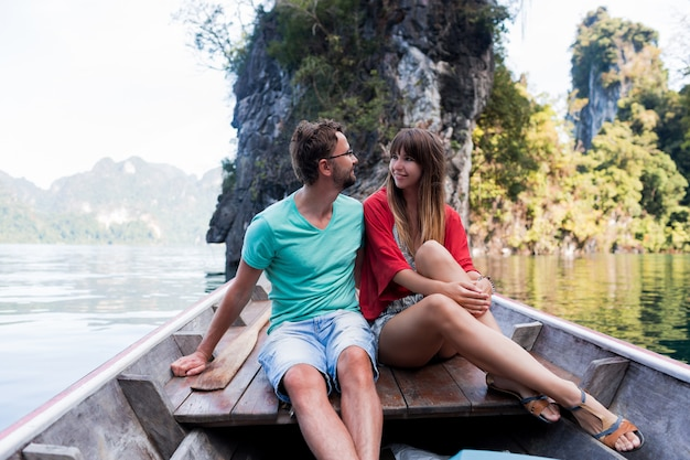 Traveling couple in love hugging and relaxing on longtail boat in thai island lagoon. pretty woman and her handsome man spending vacation time together . happy mood. adventure time.