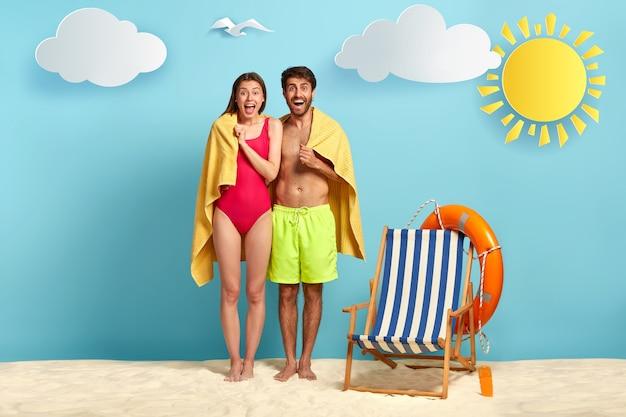 Путешествующая пара вместе стоят под одним полотенцем