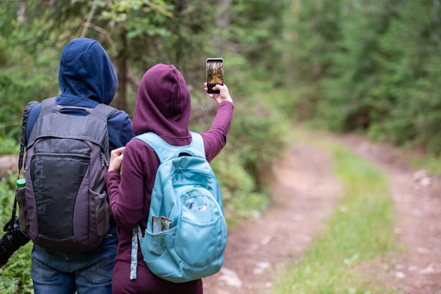 Traveling couple taking photo of forest landscape with smartphone