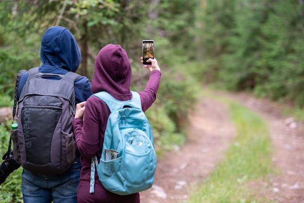 スマートフォンで森の風景の写真を撮る旅行カップル