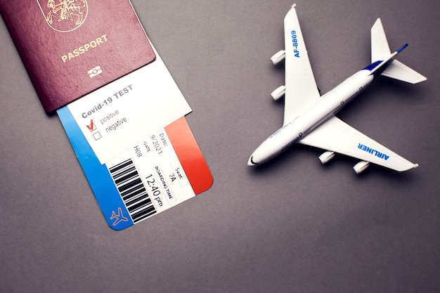Covid-19パンデミック中の旅行、航空券付きパスポート、covid-19陽性テストと灰色の背景の飛行機、空港のセキュリティの健康と安全チェックの概念