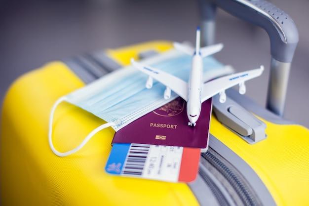 Covid-19 전염병 동안 여행. 노란색 수하물, 의료 마스크, 티켓 및 장난감 비행기가 있는 여권.