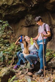 Путешествующие друзья с рюкзаками отдыхают в зеленых джунглях с напитком