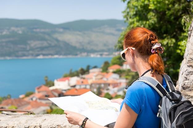 Путешествующая девушка с картой в европе читает карту