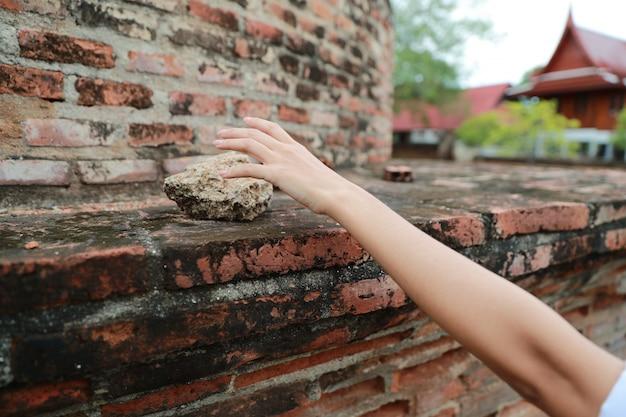 古代寺院の岩を盗もうとする旅の手