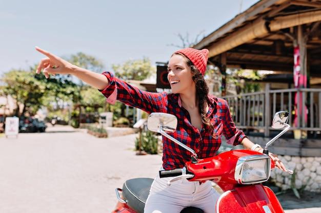 Donna graziosa in viaggio felice in camicia a quadri, berretto rosa e jeans bianchi che guida sulla sua bici rossa ai tropici in una giornata di sole