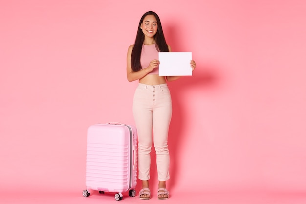 여행, 휴일 및 휴가 개념. 아시아 귀여운 교환 학생의 전신이 여행 가방을 들고 나라에 도착하고, 종이 한 장을 들고 웃으며 공항에서 호스트 가족을 찾습니다.