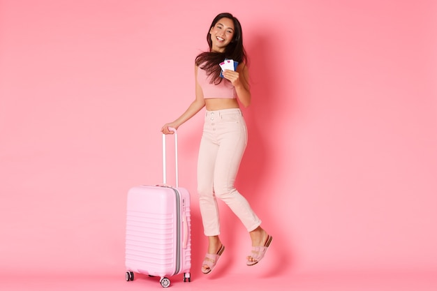 旅行、休日、休暇の概念。幸せな笑顔のアジアの女の子のフルレングス、航空券とパスポートを持つ観光客、夏の楽園、ピンクの壁の準備ができて興奮からジャンプ
