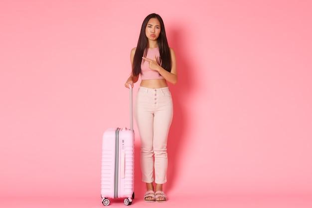 여행, 휴일 및 휴가 개념. 어리석은 매력적인 아시아 여자 친구의 전체 길이가 징징 대고 화를 내고 나쁜 서비스를 불평하며 손가락을 왼쪽으로 가리키며 가방을 들고 서 있습니다.