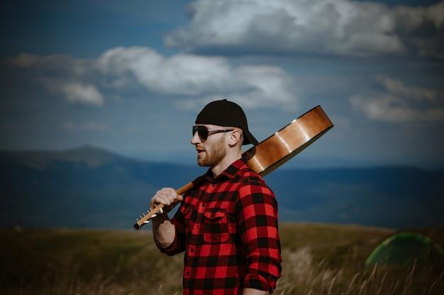 山の風景の近くでギターを持って旅行ホップスター男ハイカー男