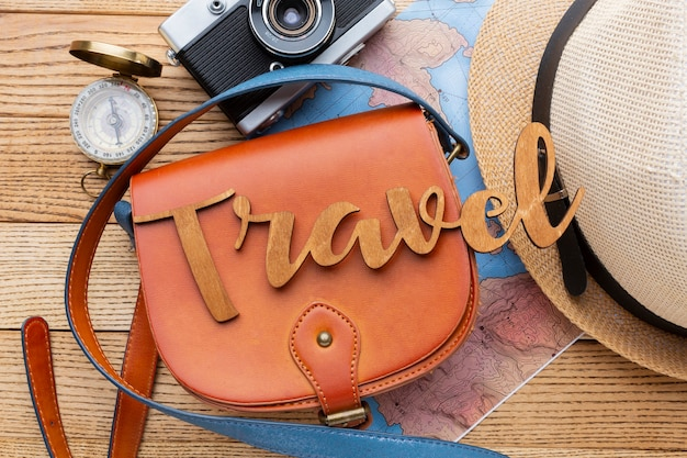 Traveling items on wooden background top view
