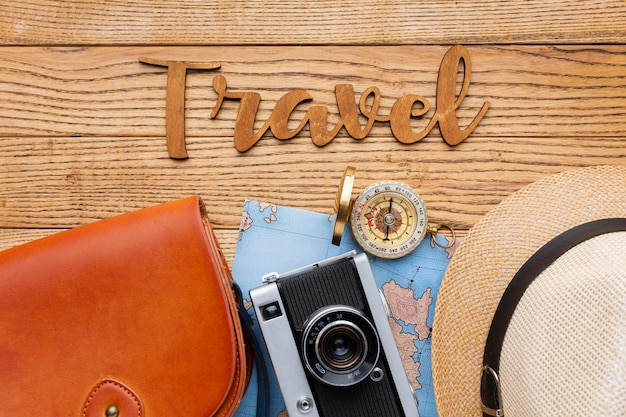 Traveling items on wooden background above view