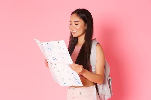 旅行、ライフスタイル、観光の概念。魅力的なアジアの女の子の観光、地図を見てバックパックを持つ旅行者の側面図、都市を探索、観光やホステルの検索、ピンクの壁