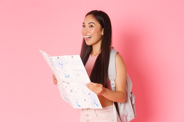 Traveling, lifestyle and tourism concept. side view of attractive asian girl tourist, traveller with backpack looking at map, explore city, going sightseeing or searching hostel, pink wall