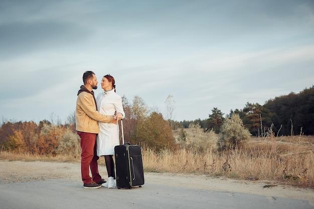 空の道でスーツケースを持って旅する男女