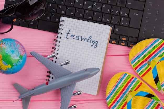 女性の旅行者のアクセサリーのメガネの財布とピンクのテーブルのフリップフロップとノートブックで旅行する...