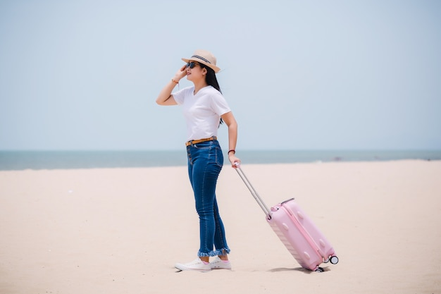 Traveling people concept. young happy asian gril at the beach