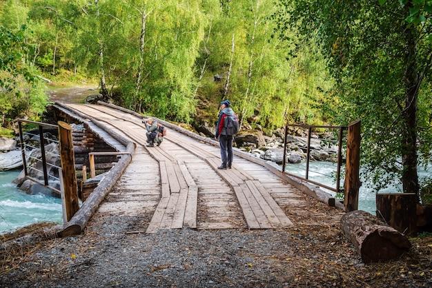 추야강의 목조 다리에서 여행하는 사진 작가는 거대한 강 급류의 사진을 찍습니다.