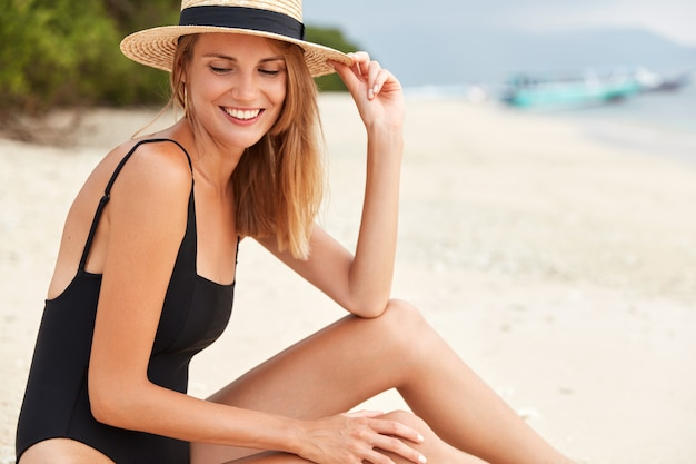 Traveling, recreation and vacation concept. happy slim fit healthy woman in bathing suit, spends free time on desert sandy beach with cheerful expression, glad have good rest
