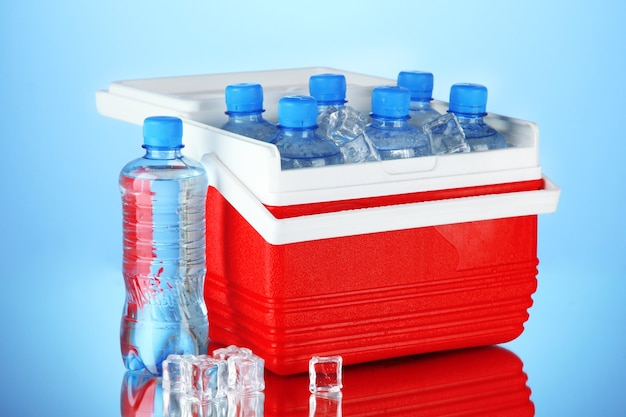 Traveling refrigerator with bottles of water and ice cubes, on blue