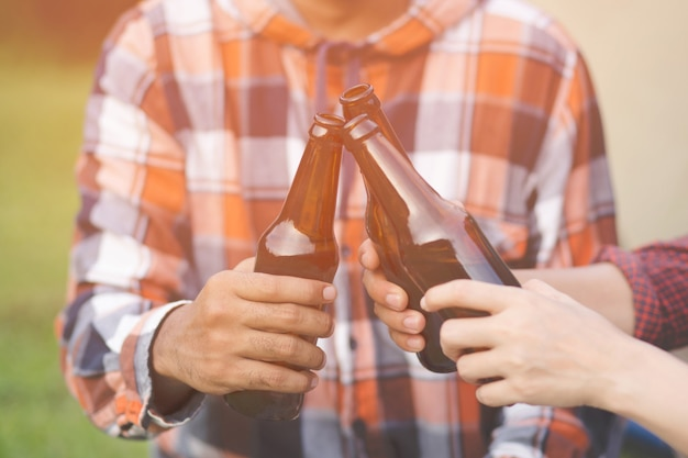 Traveling three young friends having fun together relax in hiking camp and drinking beer cheers bottles