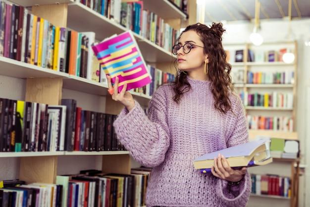 Путешествие по библиотеке. серьезная сконцентрированная девушка с раскрытой книгой в поднятой руке во время посещения книжного магазина