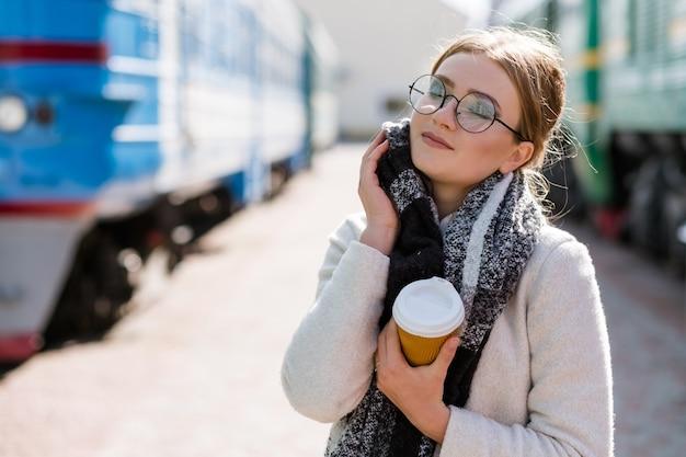 旅行のヒント。観光休暇の旅。居心地の良い服と熱いコーヒーで暖かく過ごしましょう。駅の女性