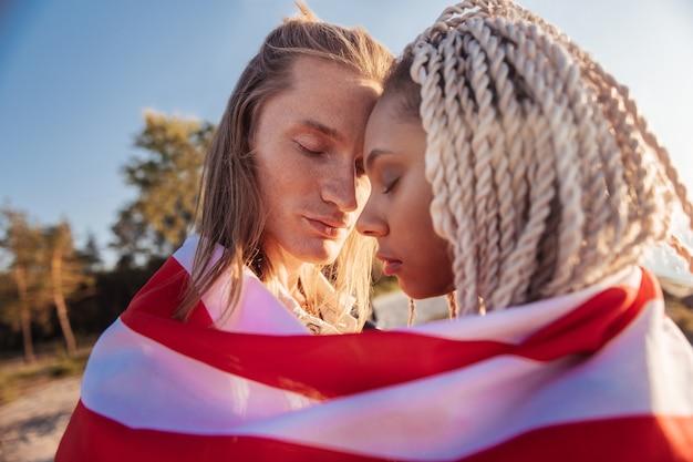 Путешествуем вместе. крупным планом симпатичная красивая влюбленная пара, путешествующая вместе со своим национальным флагом
