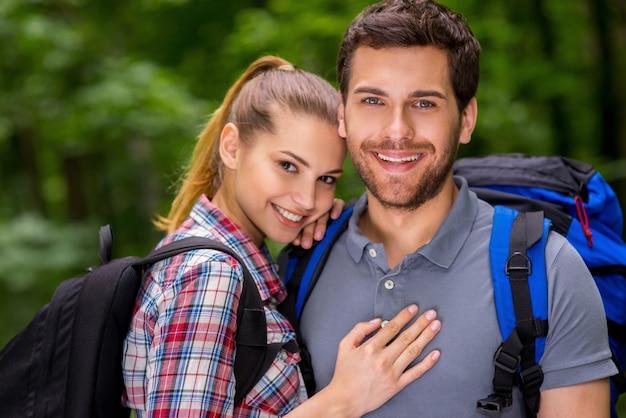 Путешествовать вместе - это весело. красивая молодая влюбленная пара с рюкзаками, глядя в камеру и улыбаясь, стоя на природе