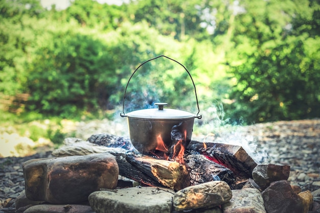 Путешествие, туризм, приготовление пикника, приготовление пищи в казане на костре.