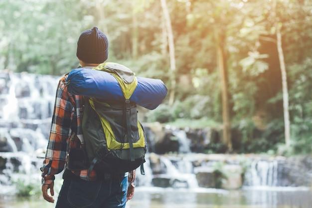 Путешествующий туристический мужской рюкзак, смотрящий на удивительные тропические горы