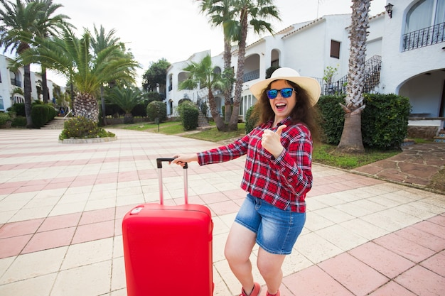 Путешествие, отпуск, праздники, поездка и концепция людей - женщина-турист с чемоданом показывает палец вверх