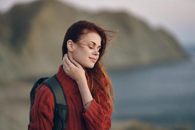 自然の海の近くの山で赤いセーターを背負ってバックパックを背負って旅行