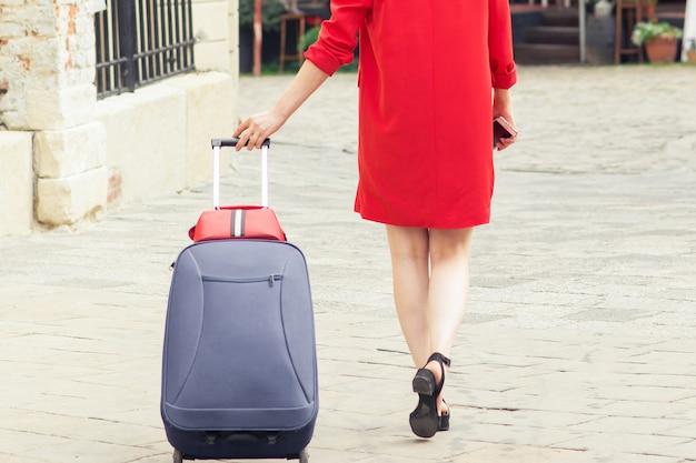 街の通りでスーツケースを持って歩く黒い帽子をかぶった旅行女性。