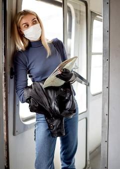 マスクと電車の中で旅行する女性
