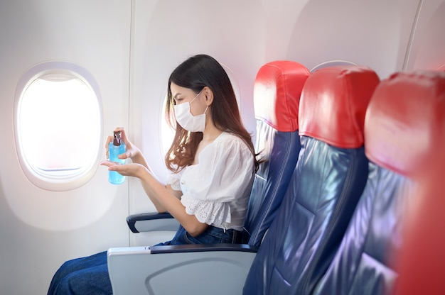 A traveling woman is wearing protective mask is washing hands with alcohol gel onboard in the aircraft, travel under covid-19 pandemic, safety travels concept