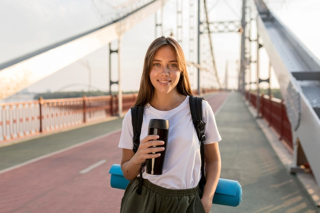 Traveling woman posing on bridge with thermos and backpack