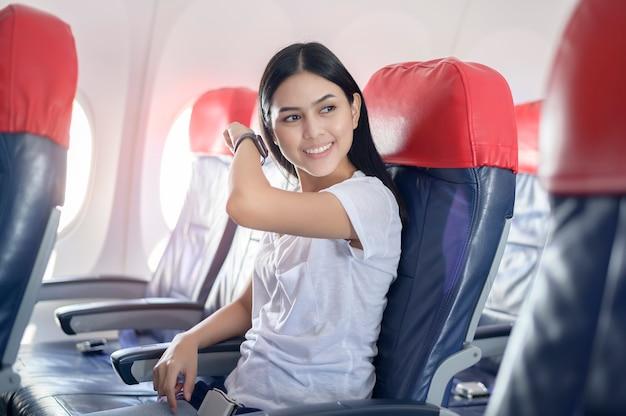 機内で旅行する女性、テクノロジー旅行のコンセプト