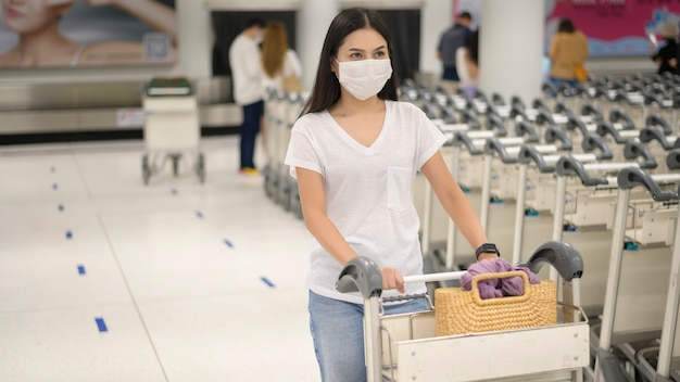 A traveling woman wearing protective mask in the airport with luggage on trolley, travel under covid-19 pandemic, safety travels, social distancing protocol, new normal travel concept
